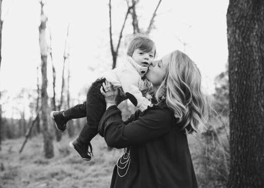 grayscale-photo-of-woman-kissing-toddler-on-cheek-standing-821529