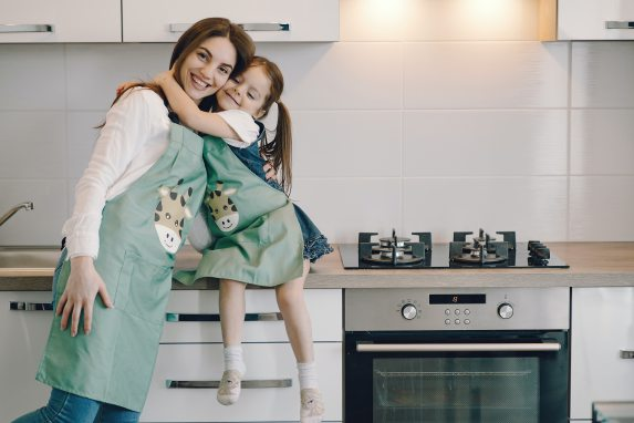 photo-of-girl-hugging-her-mom-while-sitting-on-kitchen-4149029